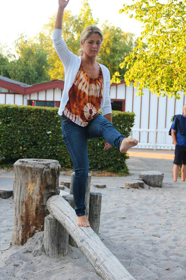 Louise Koch balances on a wooden beam in a park