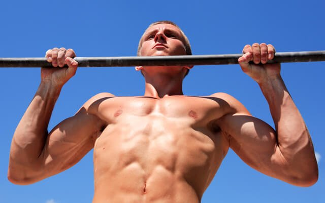 Man completing a pull-up outside