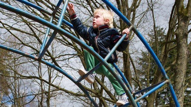 A boy climbs at a playground