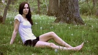 Deanna Husk relaxes in a field with her legs outstretched