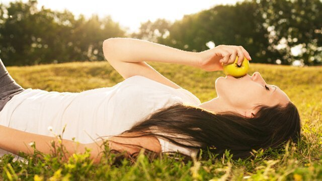 Young woman eating an apple in a grassy field