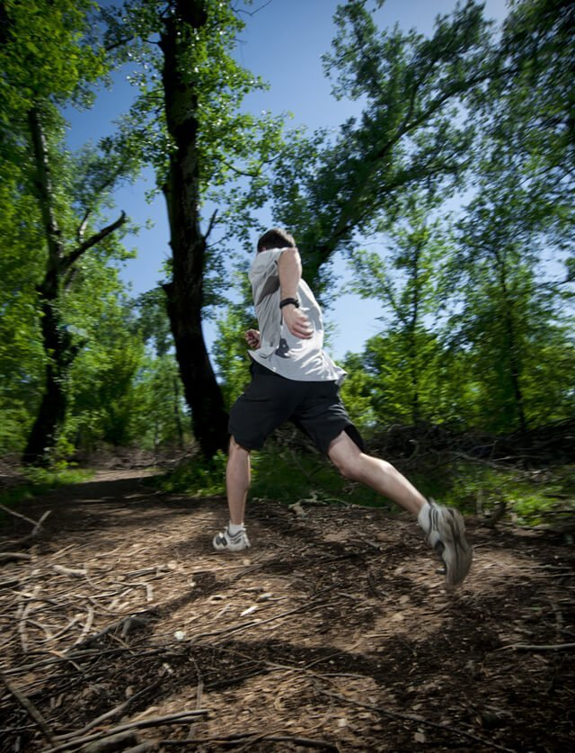 A man runs along a path in woods