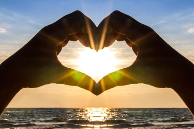 A man's hands cradle the sun in the shape of a heart