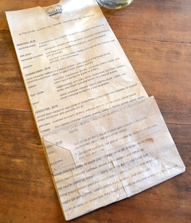 A menu printed on a paper bag at Nucleus Raw Foods