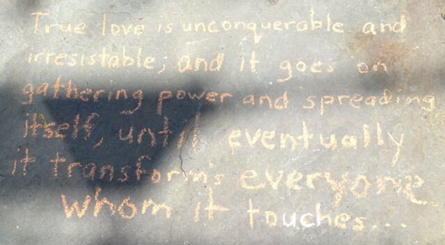 A quote is written in chalk on a walkway outside Nucleus Raw Foods