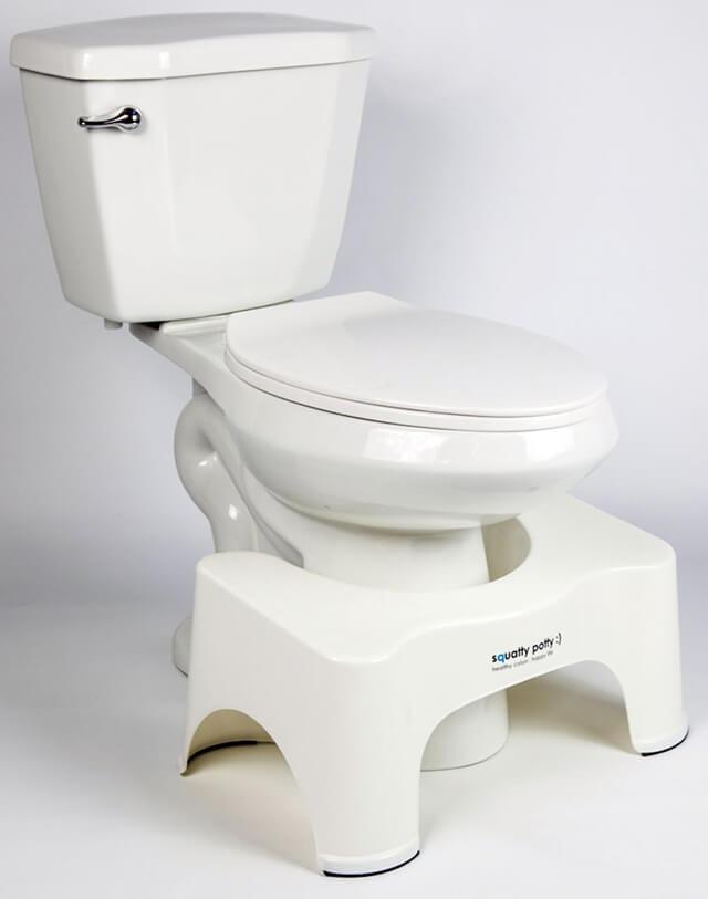 A Squatty Potty Ecco model next to a toilet