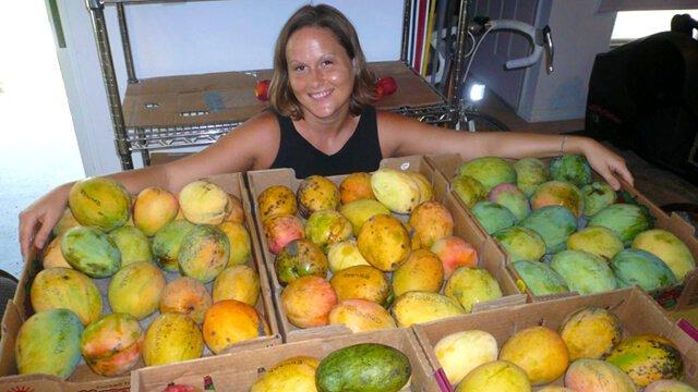 Tasha Lee playfully poses behind a lavish fruit spread