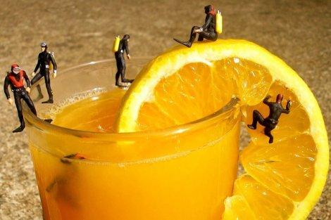 Fruit art by Anne Osborne - scuba divers inspect orange juice - Fruit-Powered