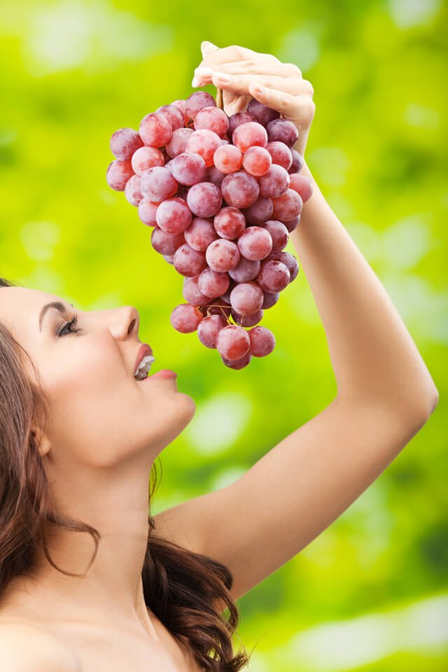 A woman playfully eats grapes outdoors