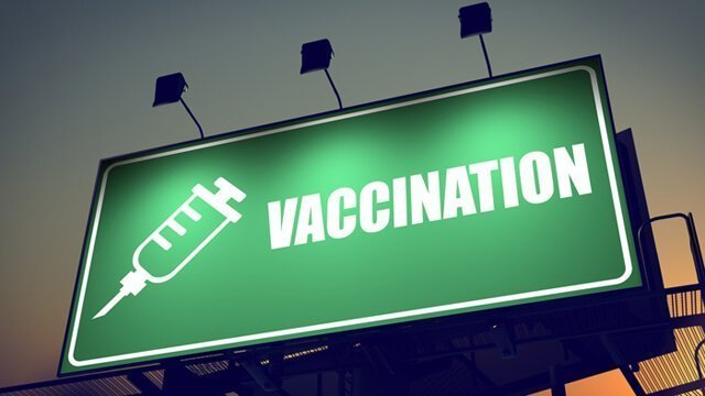 "A billboard emblazoned with the word ""Vaccination"" and a needle"