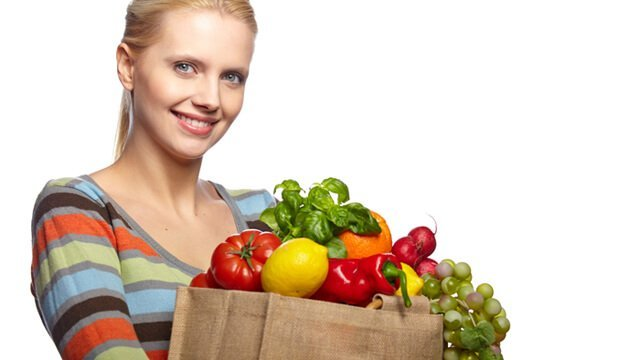 A woman holds a bag full of fruits and vegetables