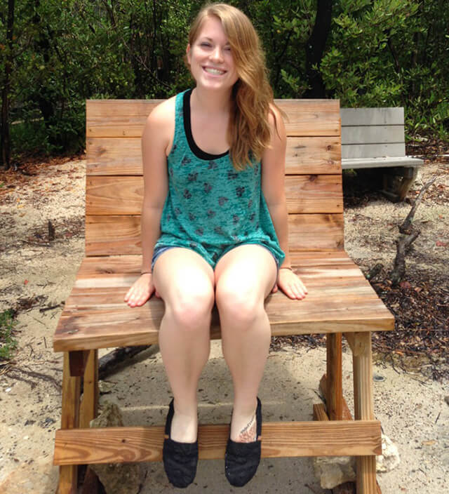 Stephanie Kent sits in a large wooden chair