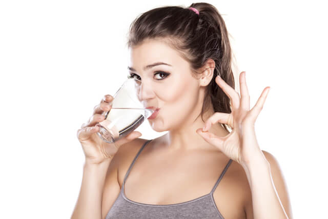 A woman drinks a glass of water