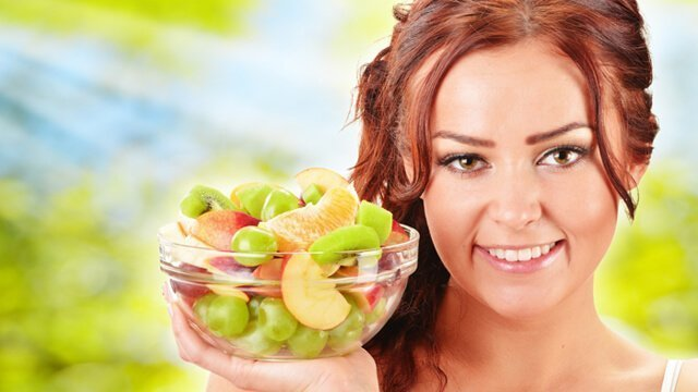 Young woman holding a glass bowl with fruit salad