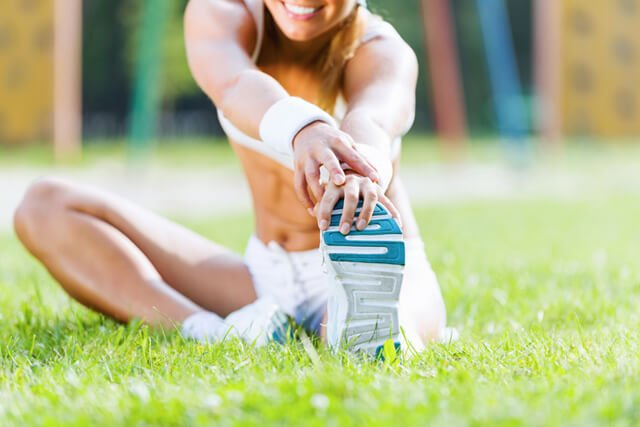 Woman stretches on grass before running