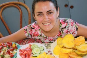 Jesi DiPalo surrounded by fruits on a table - Raw Vegan Transformations - Fruit-Powered