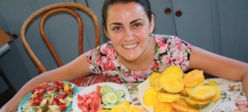 Jesi DiPalo surrounded by fruits on a kitchen table