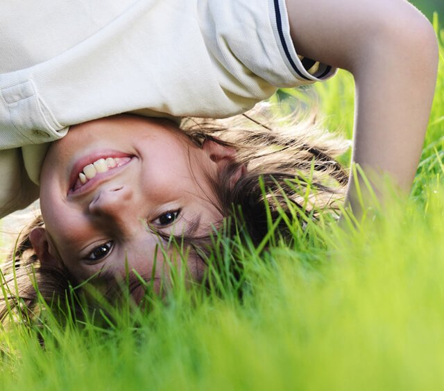 Boy plays in grass upside-down