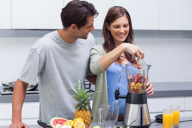 A couple prepares a fruit smoothie