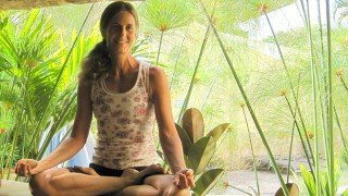 Ellen Livingston smiles while in cross-legged meditation pose