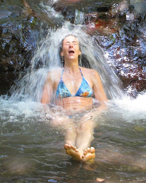 Ellen Livingston getting splashed under a waterfall