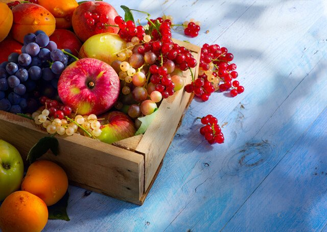Colorful fruits in a box on a deck