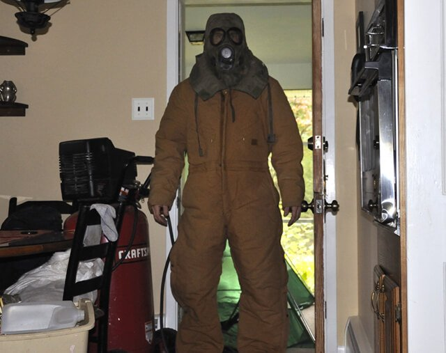 Korey Constable wears a protective outfit, gas mask and goggles to avoid mold exposure