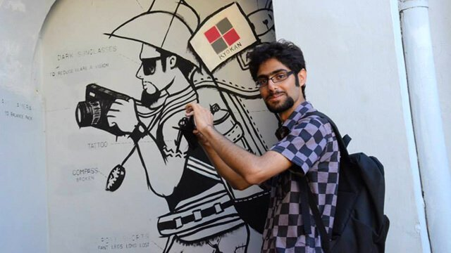 Moein Nejad holds a camera in front of a painting