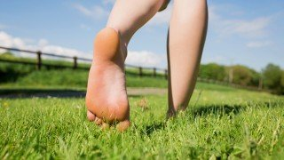 A woman's feet walking away on grass