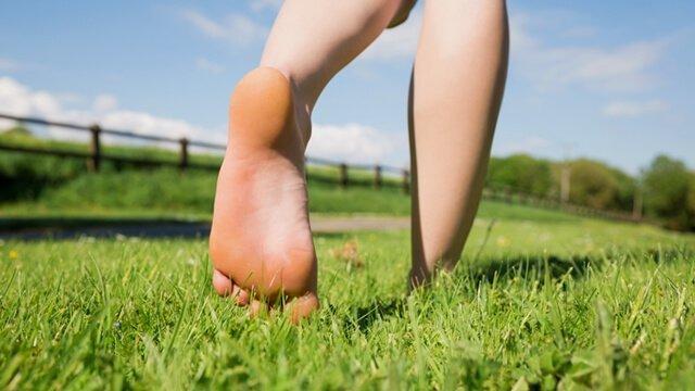 A woman's feet walking away on grass