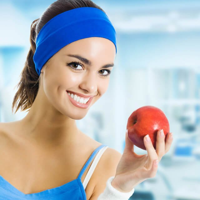 Woman holds an apple at a gym