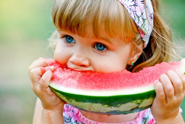 Young girl enjoys a large slice of watermelon outdoors