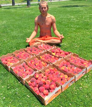 Evan Rock meditates beside boxes of peaches