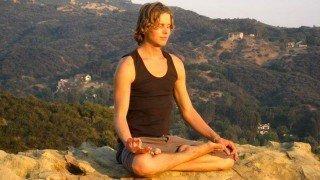Evan Rock meditates in a hilly region