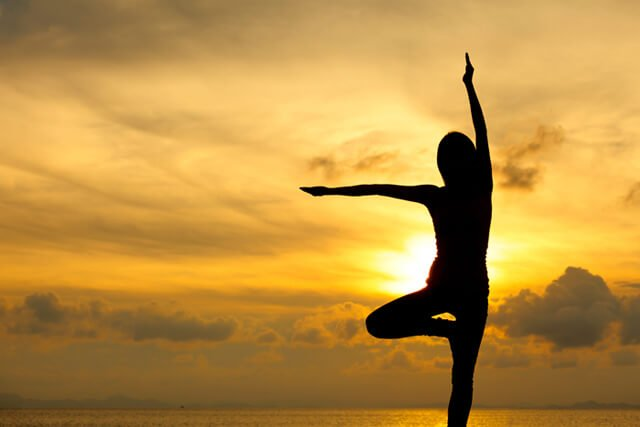 Silhouette of a woman practicing yoga by the sea at sunset