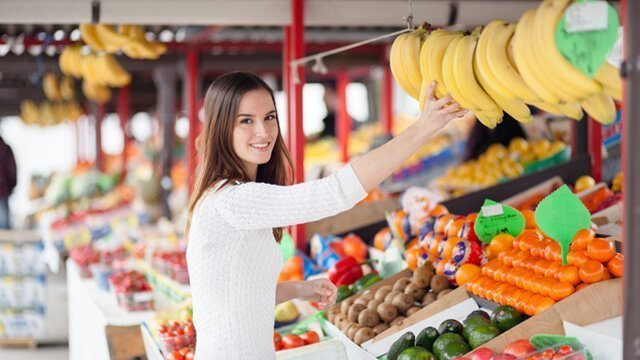 Young woman buying bananas at a market