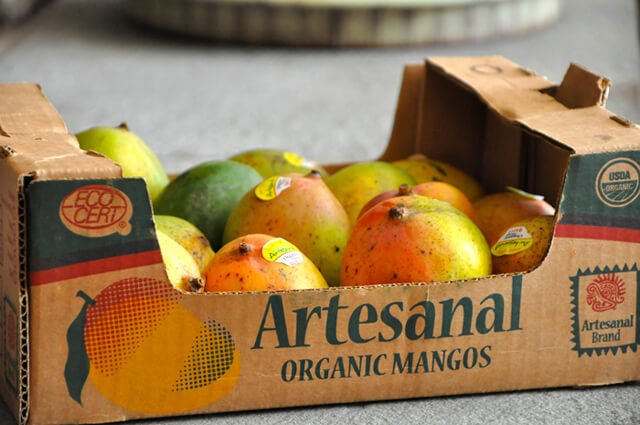 A box of organic mangos on a floor