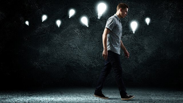 Man walking in the dark with lightbulbs guiding his way