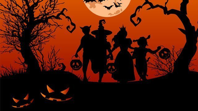 Silhouettes of children trick-or-treating in Halloween costumes