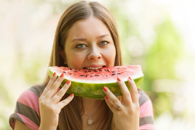 Woman eating a large seeded watermelon slice outside