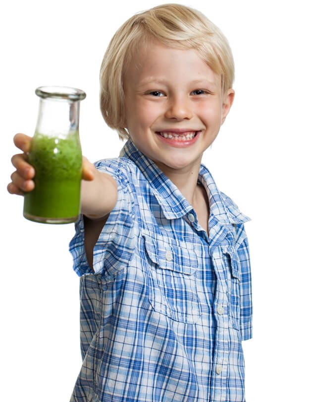 A boy smiles while holding a green juice