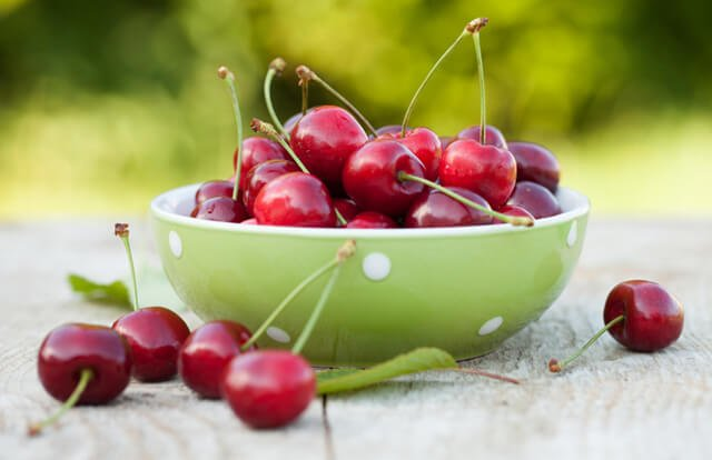 Fresh cherries in a bowl on a garden table