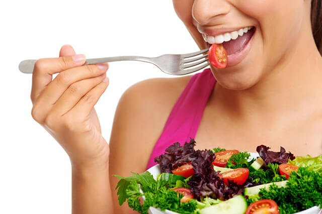 A woman eats salad in a closeup photograph