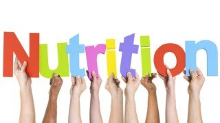 """Hands hold up colored letters to spell the word """"nutrition"""""""