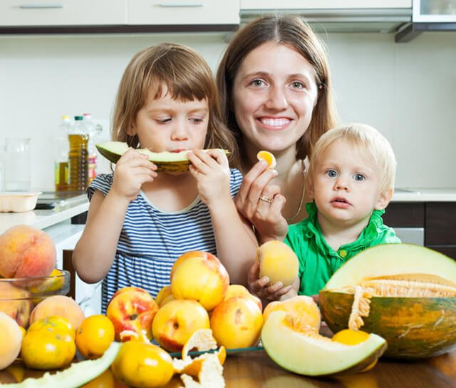 Mom and children enjoy fruit in a kitchen