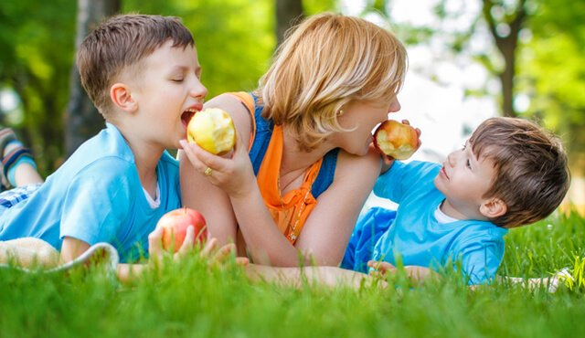 A mom and her sons playfully eat apples in a field