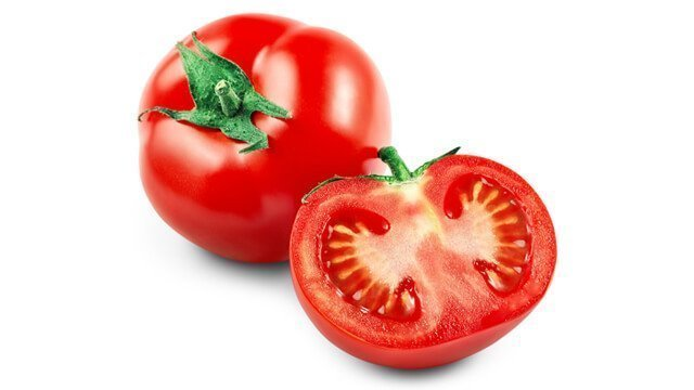 Whole and halved tomatoes against a white background