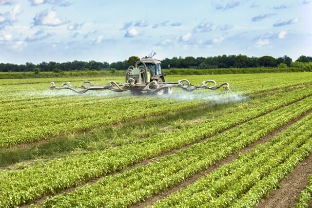 A tractor sprays pesticides on a large farm