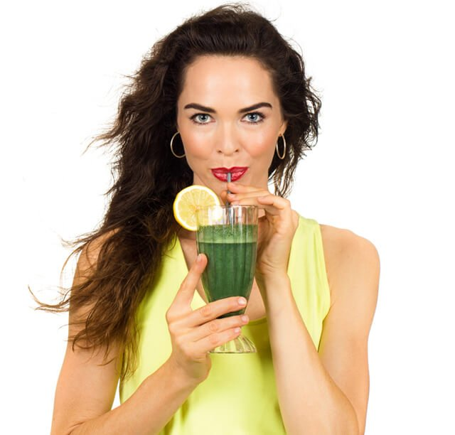 Woman drinks a green juice from a straw