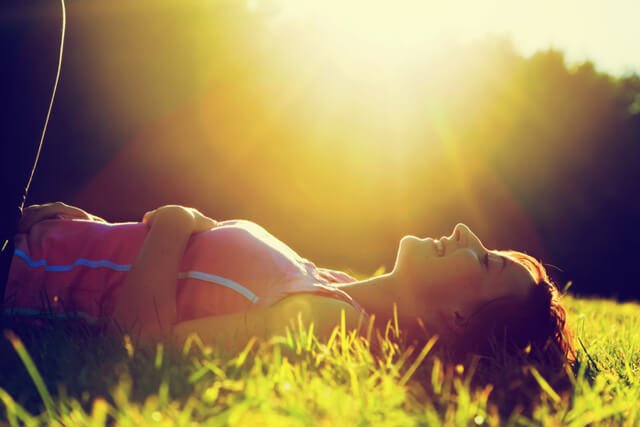 Woman smiles as the sun sets while laying on grass